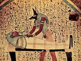 Египетский бог смерти Анубис склонился над мумией
